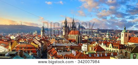 Top view of Prague, Czech Republic. Panoramic view of old town Church of Our Lady Before Tyn and Gothic cathedral on city skyline with scenic sunset and blue sky. Midtown castle red roofs.
