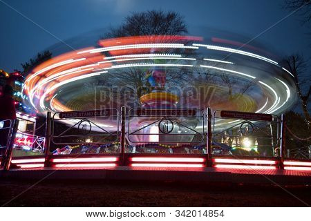 READING, UK - DECEMBER 27, 2019: Bright lights on a thrill ride at a Christmas funfair in Reading, Berkshire, UK.