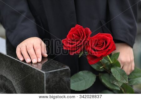 Woman With Red Roses Near Black Granite Tombstone Outdoors, Closeup. Funeral Ceremony