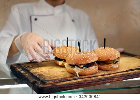 School Canteen Worker With Burgers At Serving Line, Closeup. Tasty Food