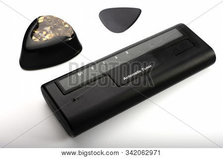 Tuner For Tuning A Six String Guitar Picks On A White Background