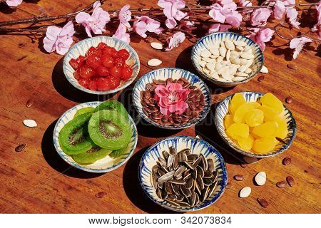 Bowls With Various Seeds And Dried Fruits And Berries On Wooden Table Served For Tet