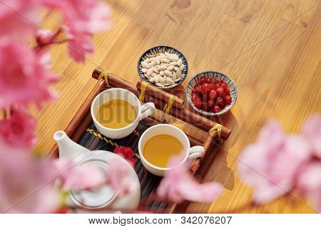 Two Cups Of Tasty Green Tea And Dried Berries And Seeds As Traditional Treat For Tet Celebration