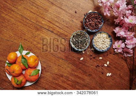 Flatlay Of Table Served For Tet Celebration With Plate Of Tangerines And Bowls With Seeds