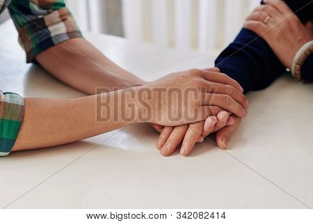Close-up Image Of Young Man Holding Hand Of His Mother When Reassuring Her