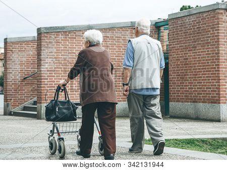 An Elderly Couple Or Senior Citizens Strolling Or Walking Along A Pedestrian Road.