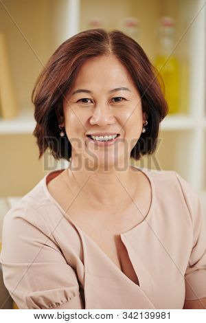Portrait Of Happy Pretty Middle-aged Vietnamese Woman Smiling At Camera