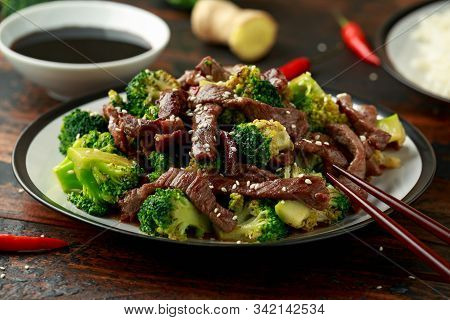 Homemade Beef And Broccoli With Rice And Herbs On Wooden Table