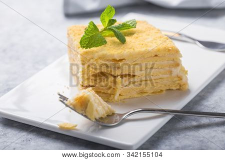 Piece Of Cake Napoleon On White Plate On Concrete              Background, Close Up View. Traditiona