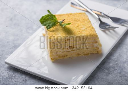 Napoleon Cake.piece Of Cake Napoleon On White Plate On Concrete Background, Close Up View. Tradition