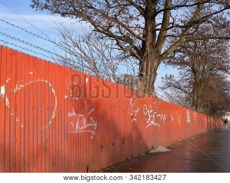 Chomutov, Czech Republic - December 16, 2019: Big Tree Behind Iron Red Fence During Christmas