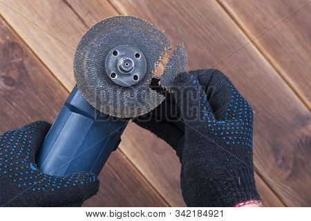A Grinder With A Broken Blade On A Wooden Table. The Danger Of Using Power Tools.