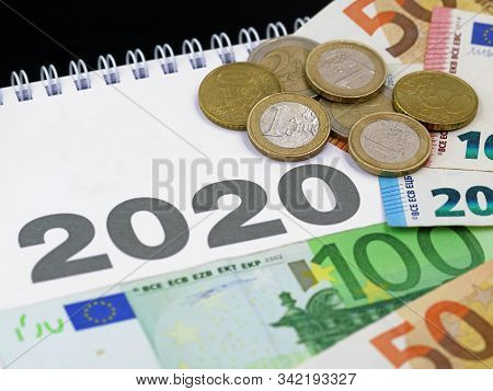 Euro Banknotes And Coins On Calendar 2020, Concept Of Expenditure Or Taxes Payment, Cost In The New