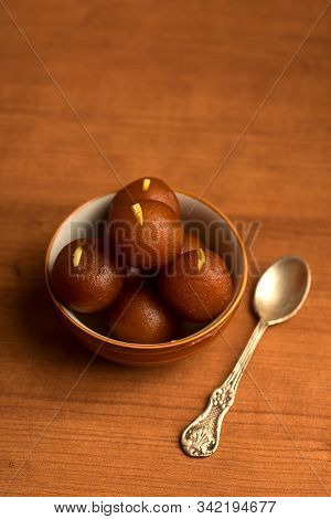 Gulab Jamun in bowl on wooden background. Indian Dessert or Sweet Dish. poster