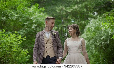 Wedding Couple In The Park. Bride And Groom.love Of Two People.bride And Groom Hugging And Smyling A
