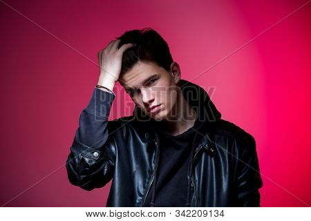 Cute Brutal Man In Black Leather Jacket Model Style. Portrait Of A Handsome Guy On Pink Studio Backg