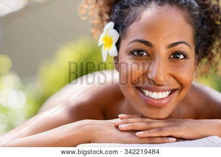 Closeup face of young african american woman in a wellness center ready for massage therapy. Portrait of beautiful girl lying down on massage table at spa resort. Smiling beauty girl looking at camera