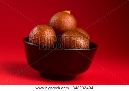 Gulab Jamun in black bowl on red background. Indian Dessert or Sweet Dish. poster