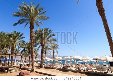 Eilat, Israel - March 37, 2019: Beach With Palm Trees, Sunshades And Sunloungers At Red Sea. Eilat I