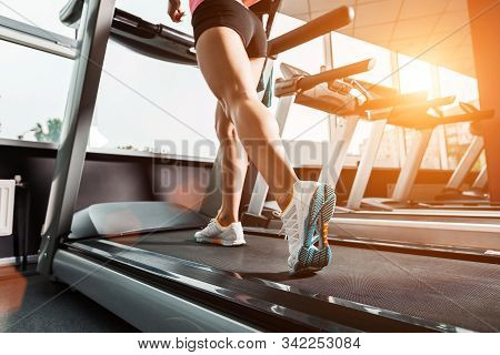 Close Up Girls Feet Walking At The Treadmill In The Gym Over Sunrise. Wearing In White Orange Blue S