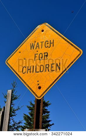 """Old """"Watch For Children"""" sign on a metal post and riddled with bullet holes poster"""