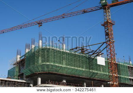 Crane And Building Construction Site Against Blue Sky. Metal Construction Of Unfinished Building On