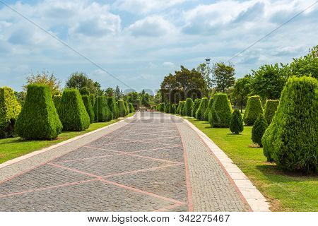 Cobbled Walkway In A Park With Bright Green Clipped Trees, Blue Sky And Beautiful Clouds. Regular Pa