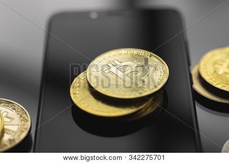 Golden Bitcoin Coin On A Smartphone With A Lot Of Bitcoins Coins On A Table. Virtual Cryptocurrency