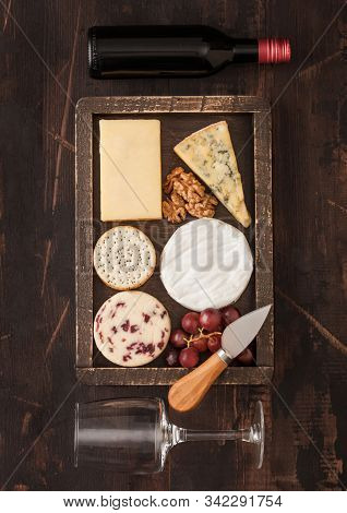Glass And Bottle Of Red Wine With Selection Of Various Cheese In Wooden Box And Grapes On Wooden Bac