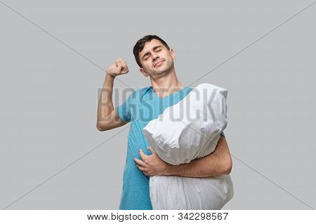 Young Brunet Man Stretching Holding White Pillow Isolated Over Grey Background. Being Tired After Lo