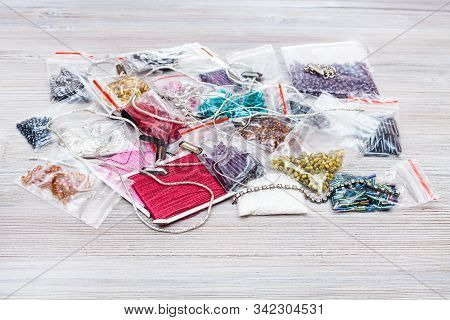 Pile Of Various Items, Beads, Bugles, Spangles, Threads, Gimps For Embroidery On Gray Wooden Board C