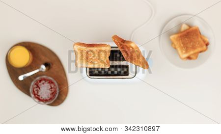 Slices Of Toasted Bread Flew Out Of The Toaster. Near Glass Of Orange Juice, Bowl With Strawberry Ja