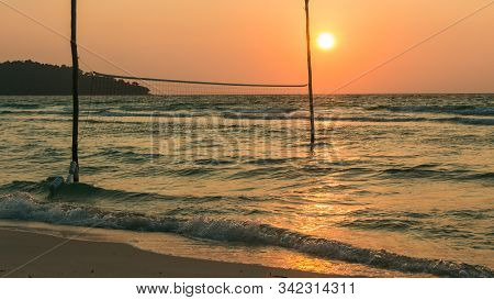 A Volleyball On The Beach At Sunrise