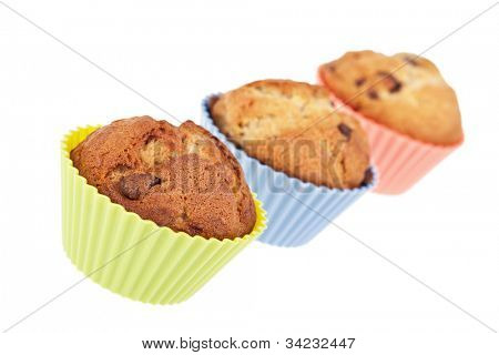Three chocolate chip banana muffins in bright silicone cases. Intentional shallow Depth of Fie;d.