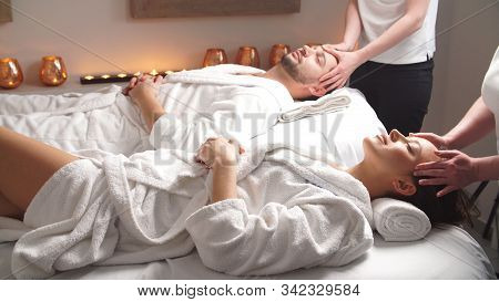 Beautiful Couple Lying Down On Massage Beds Enjoying A Head Massage In Luxury Spa. Relaxing And Heal