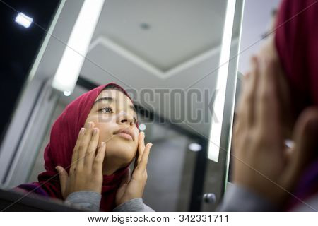 Muslim beautiful girl looking into mirror checking face skin
