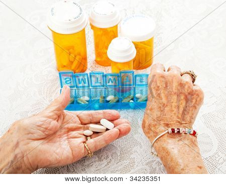 Closeup view of an eighty year old senior woman's hands as she sorts her prescription medicine.