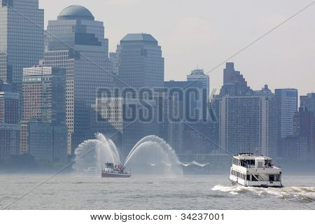 HOBOKEN, NJ - MAY 23: A NY Waterway ferry and Fireboat Harvey on the Hudson River near Manhattan during the Parade of Sails on May 23, 2012 in Hoboken, NJ. The parade marks the start of Fleet Week.