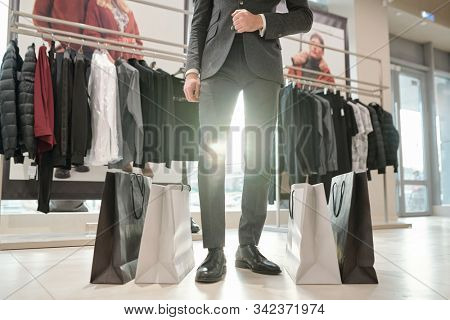 Low section of elegant man in suit standing on the floor between paperbags inside contemporary boutique