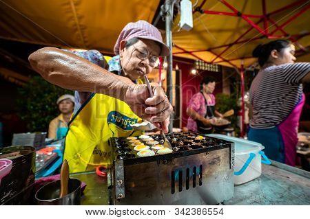 Krabi Town, Thailand - November 23 2019: An Elderly Thai Woman Prepares Fried Quail Eggs Off Bird  I