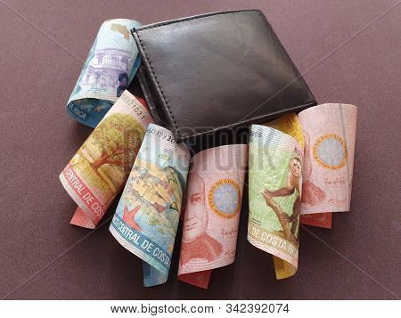 Black Leather Wallet And Costa Rican Banknotes Of Different Denominations