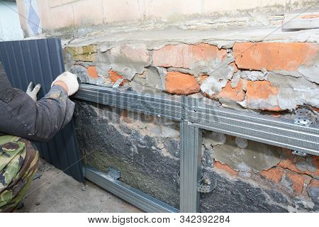 Brick House Foundation Wall Repair,  Renovation  With Builder Hands Installing Metal Sheets For Wate