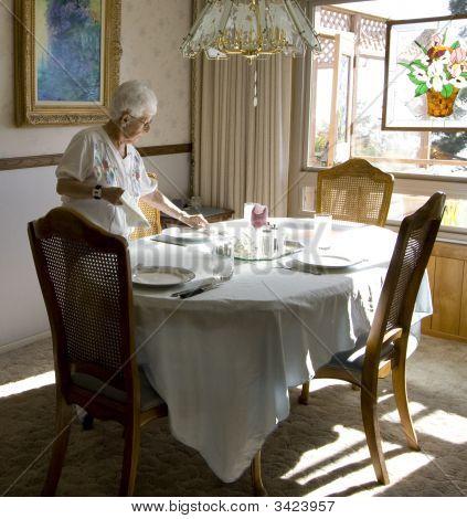 Senior Woman Sets Dinner Table