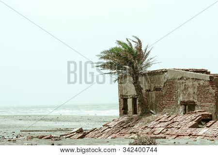 An Old Ruin Abandoned House By Sea Beach. Damaged Broken Demolished Ruined Fortified Brick Wall Buil