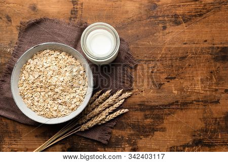 Rolled Oats, Oat Flakes And Oat Milk On Wooden Table Background, Top View. Healthy Diet Food, Clean