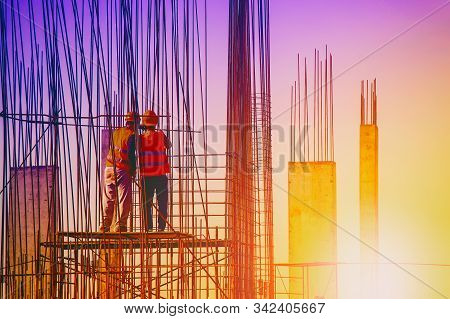 Two Male Construction Workers In Overalls Working On A Construction Site On The Background Of Sunset