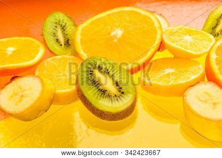 Fresh And Juicy Orange, Lemon, Banana, Kiwi Fruit Slices On The Yellow Background, Healthy Food, Veg