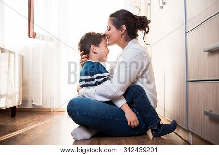 Beautiful Young Mom And Her Son, Sitting On The Floor Hugging Each Other Tightly. Mom Is Kissing Her