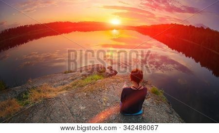 Beautiful Woman Sits In A Pose Of A Half Lotus On High Place Amazing View Of The Lake Sunset Summer