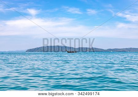 A Longtail Boat Sailing In Andaman Sea Off The Coast Of Thailand Near Railay Beach.